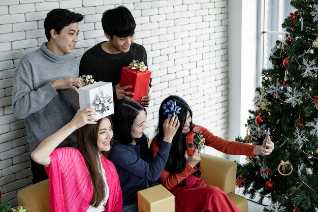 크리스마스 축제를 축하하는 집에서 선물을 가진 그룹 젊은 아시아의 셀카