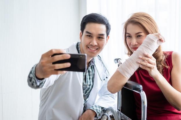 笑顔の男性医師と女性患者のセルフィーは、より良い治癒のために腕の添え木を着用し、スマートフォンを使用して車椅子に座ります。部屋の病院の背景にあります。