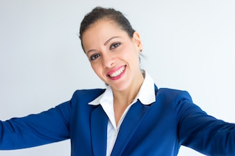 Selfie of smiling young Caucasian woman in formal suit.