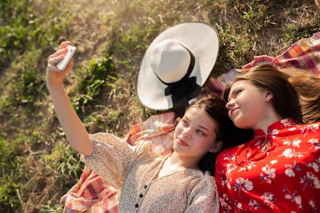 Селфи двух красивых молодых женщин на летнем пикнике
