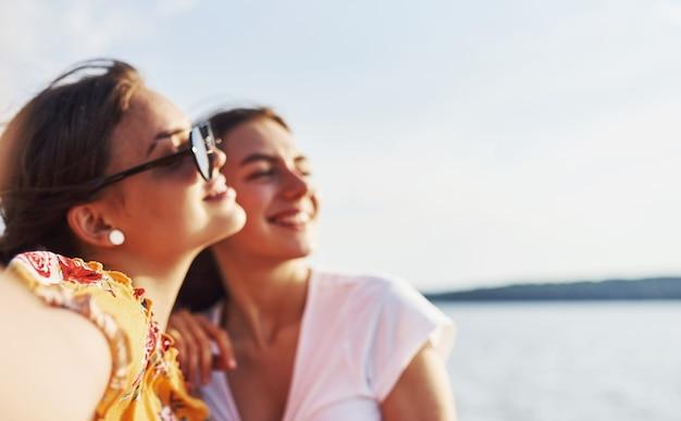 湖に対して晴れた日に一緒に良い週末を過ごす屋外の2人の笑顔の女の子の自分撮り。