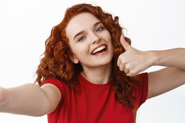 親指を立てて、スマートフォン、白い壁に笑みを浮かべて、良いものを賞賛し、お勧めする巻き毛の髪型を持つ若い幸せな赤毛の女の子の自分撮り