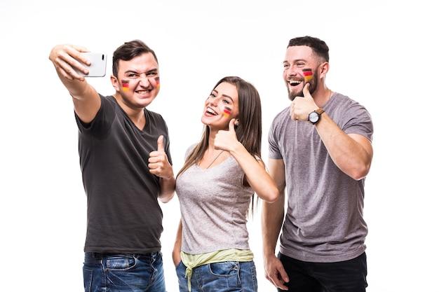 흰색 바탕에 독일 국가 대표팀의 게임 지원에 독일 축구 팬의 전화에 selfie. 축구 팬 개념.