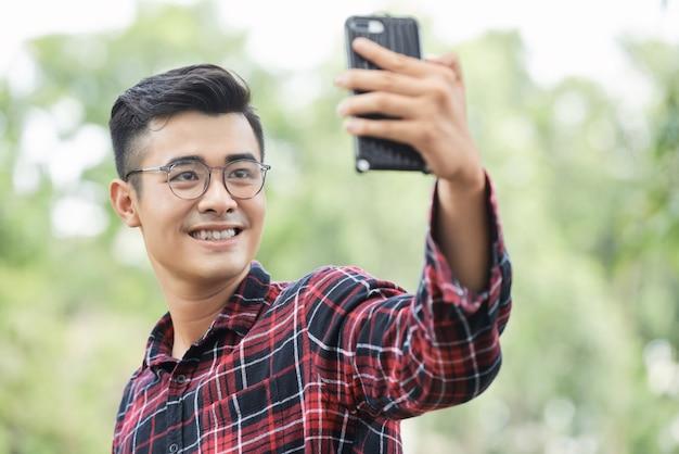 Молодой азиатский человек в стеклах принимая selfie outdoors