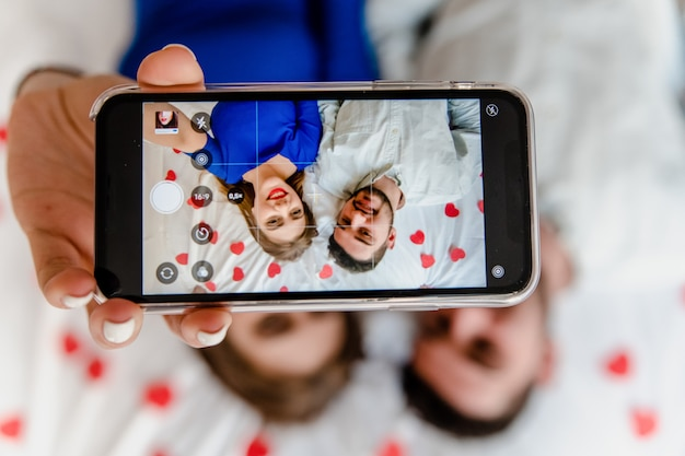 Selfie on phone screen of man and woman in love in bed