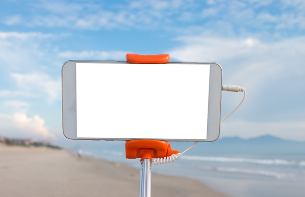 Selfie photo concept : mock up extensible selfie stick or monopod with mobile phone taking picture