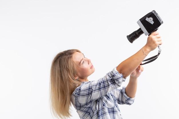 Селфи фото, фотограф и концепция ретро камеры - молодая женщина, использующая старинную камеру на белой стене.