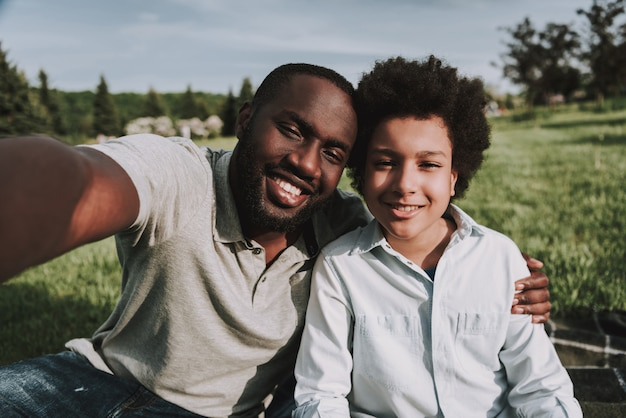 Selfie picture of afro son and father on picnic
