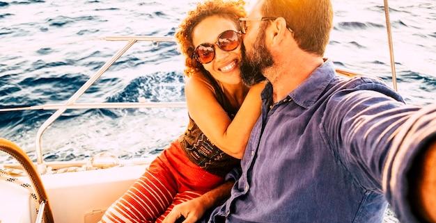 遊覧船の遠足で一緒にキスして楽しんでいる楽しいカップルと一緒に自分撮り写真-愛と観光休暇の人々の概念-背景の海の青い水 Premium写真