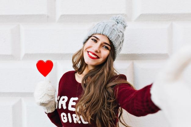 Ritratto di selfie bella ragazza con capelli lunghi in cappello lavorato a maglia con lecca-lecca cuore rosso sul muro grigio. indossa guanti bianchi caldi, sorridendo.