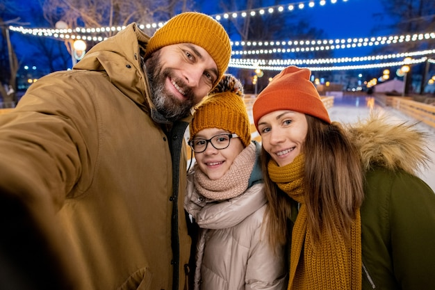 Selfie portrait of family of three smiling at camera while skating together outdoors