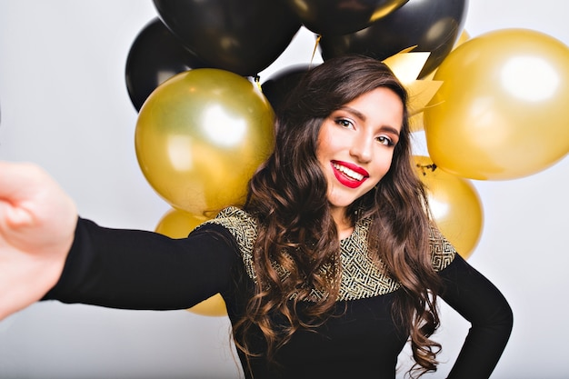 공백에 금색과 검은 색 풍선 사이의 우아한 패션 드레스에 selfie 초상화 재미 놀라운 소녀