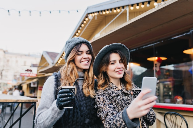 Selfie portrait of joyful fashionable women having fun on sunny street in city. stylish look, having fun, travelling with friends, smiling, expressing true positive emotions.