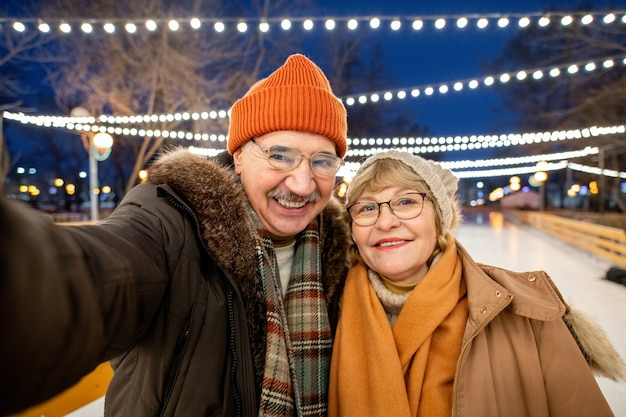 Selfie portrait of mature happy couple on ice rink outdoors