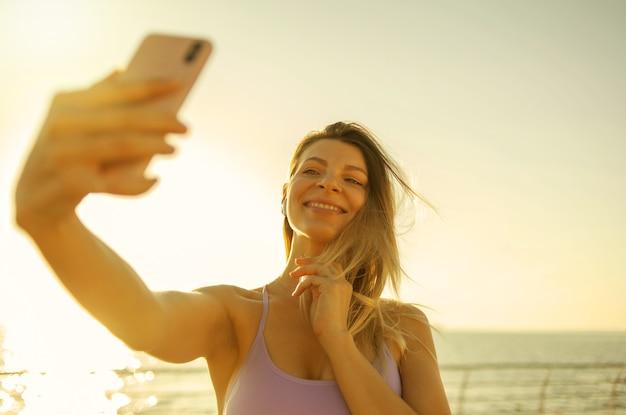 Селфи-портрет молодой блондинки, одетой в спортивную одежду на пляже на рассвете