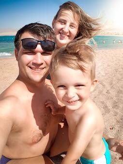 晴れた風の強い日に海のビーチで幸せな笑顔の陽気な家族の自分撮りの肖像画。家族でリラックスして夏休みに楽しい時間を過ごします。