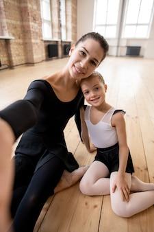Селфи-портрет женщины и маленькой девочки, позирующей перед камерой, сидя на поплавке после занятий балетом в студии