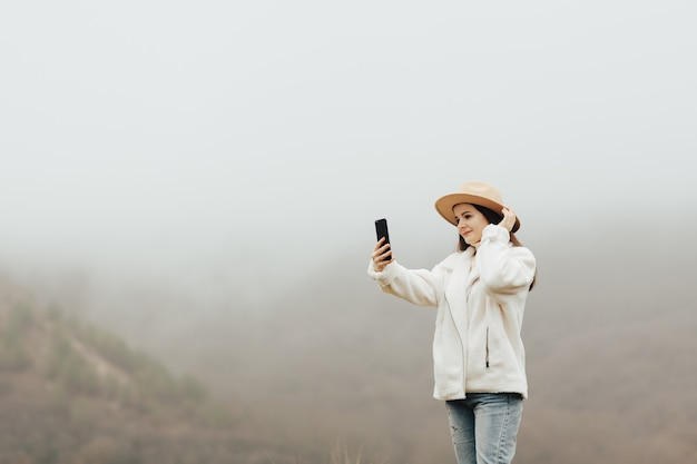 베이지 색 모자와 코트를 입고 언덕에서 안개가 자욱한 경사면에 셀카를 복용 명랑 소녀의 selfie 초상화.