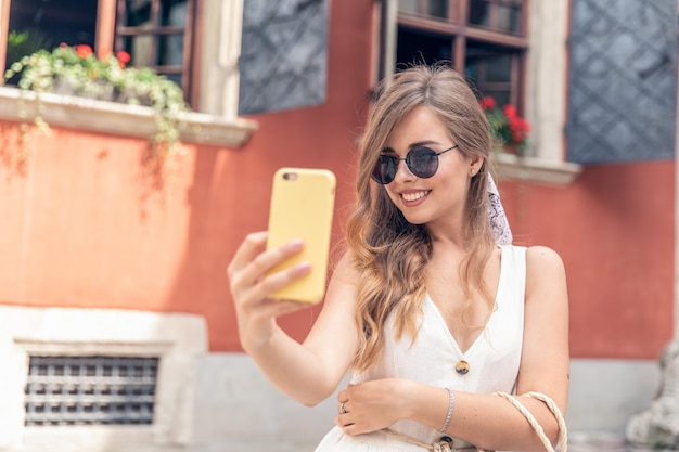 Selfie portrait of a young woman in the street with a smartphone
