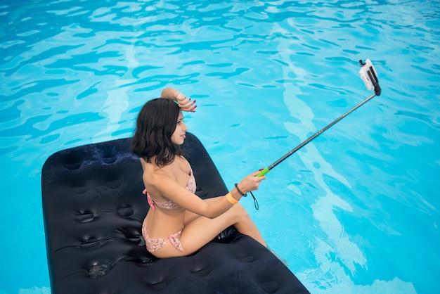 ブルネットは、プールでマットレスにselfieスティックで携帯電話でselfie写真を作ります