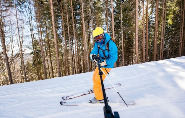 冬のスキーリゾートで山の斜面をスキーしながらselfieスティックを使用してselfie写真を撮る男性スキーヤー