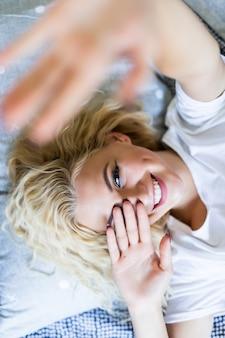 ベッドでselfieを作る美しい少女。自宅のベッドで自己を作る美しい少女。朝の自撮り。ウィンドウの前に立っている間selfieを作る美しい若い女性