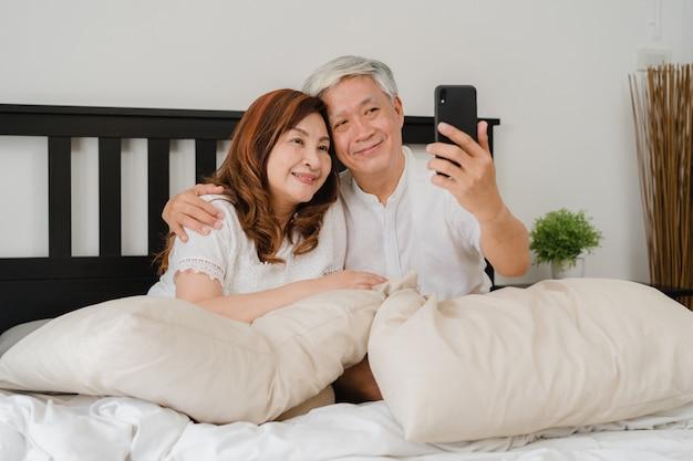 自宅でアジアシニアカップルselfie。アジアのシニア中国の祖父母、夫と妻の朝のコンセプトで自宅の寝室のベッドに横になって目を覚ます後携帯電話selfieを使用して幸せ。