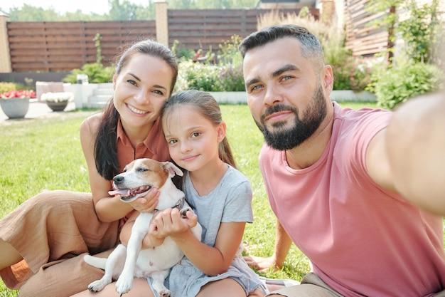 芝生の上に座って裏庭で彼らの小さな犬と一緒に時間を過ごす一人の娘と一緒に現代の家族の自分撮りショット