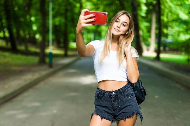 Девочка-подросток красоты принимая selfie на smartphone outdoors в парке на солнечный день.