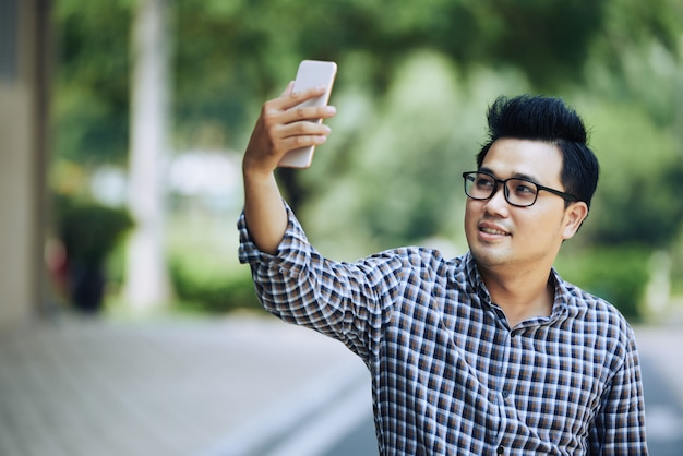Молодой азиатский человек в стеклах и клетчатой рубашке принимая selfie с smartphone