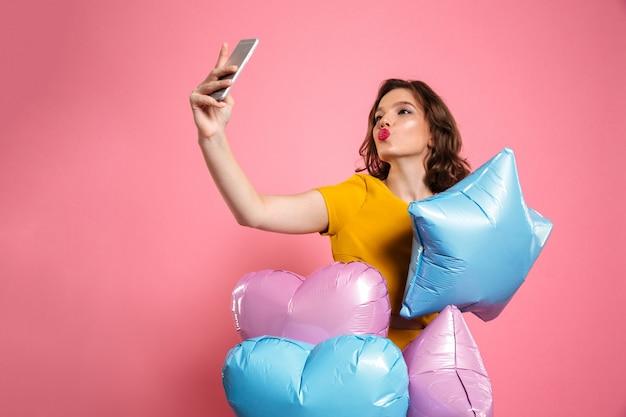 Молодая привлекательная девушка дня рождения с воздушными шарами принимая selfie на smartphone