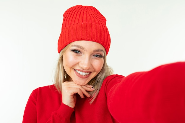 Selfie of a smiling blonde girl in a red hat and sweater on a white background