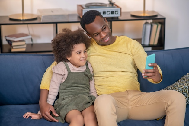Selfie. smiling dark-skinned young adult dad with little cute daughter taking selfie on smartphone while sitting on sofa in afternoon