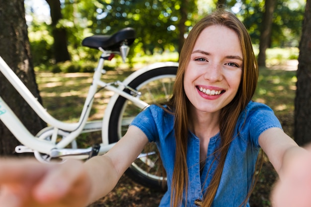Selfie of a smiling woman next to bike