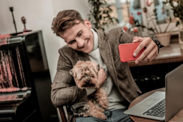 セルフィースター。小さな犬と一緒に自分撮りをする男