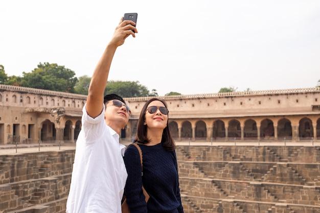 Датирующ азиатских пар счастливых в влюбленности принимая фото selfie на stepwell чанда baori в индии.