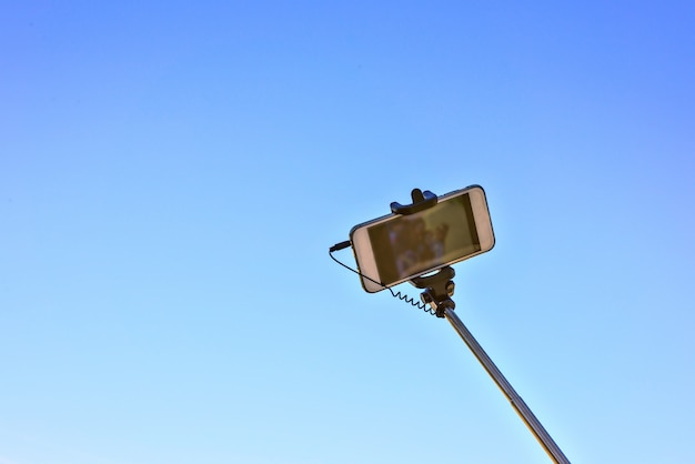Selfie stick on blue sky background. smart phone