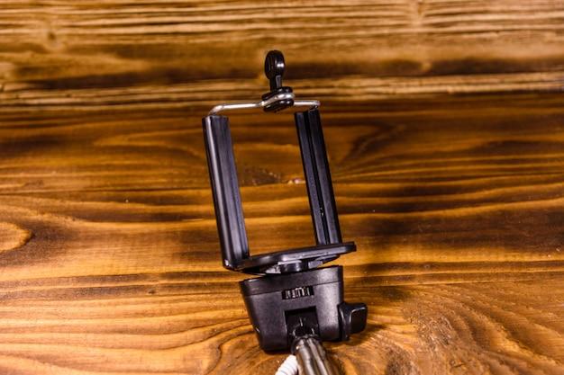 소박한 나무 테이블에 조절 가능한 클램프가 있는 셀카봉