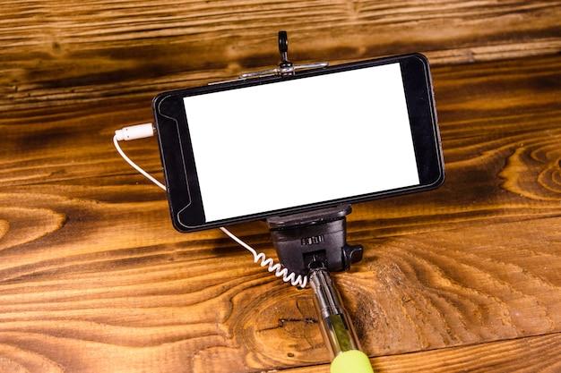 소박한 나무 테이블에 현대적인 스마트폰이 있는 셀카봉