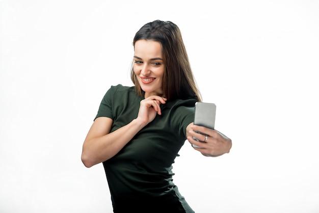 彼女のスマートフォンでselfieを作るうれしそうな若い女性。ストレートの黒髪の幸せなきれいな女の子は、幻想的な笑顔で黒のtシャツを着てselfieになります