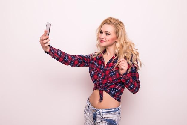 Selfieを作る短い赤いtシャツで金髪の長い髪の少女
