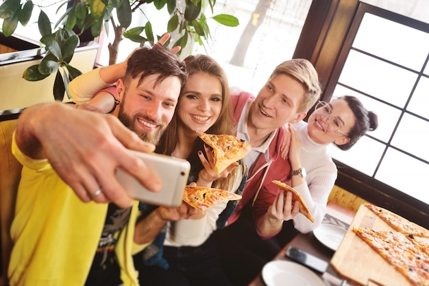 Selfie time concept. friends eat pizza in a cafe, smile and shoot themselves on the camera smartphone