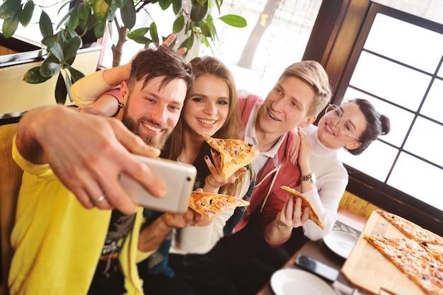 Селфи время концепция друзья едят пиццу в кафе, улыбаются и снимают себя на камеру смартфона