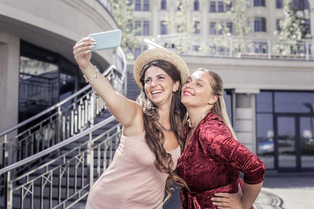自分撮りの時間。彼女の妹と写真を撮っている間彼女のスマートフォンを持っているうれしそうな幸せな女性