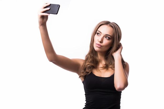 自分撮りの時間。灰色の壁に彼女のスマートフォンで自分撮りを作るうれしそうな若い女性