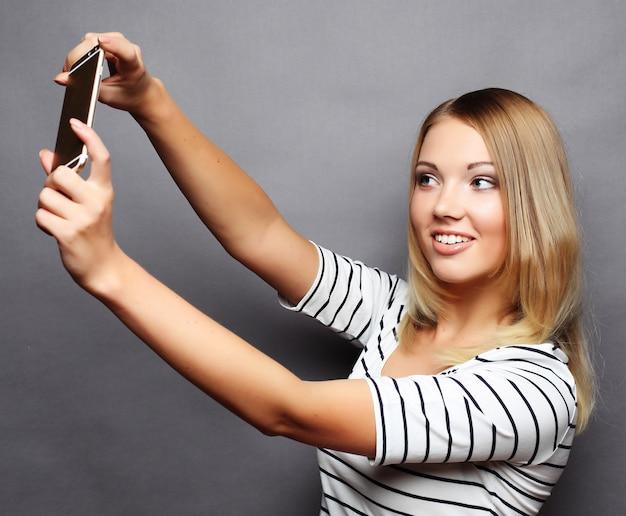 Selfie time. joyful young women making selfie by her smart phone