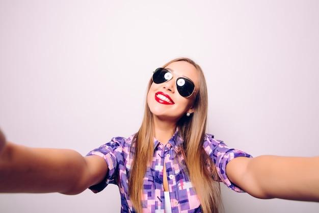 自分撮りの時間。スマートフォンで自分撮りをするうれしそうな若い女性
