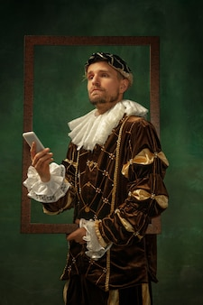 Selfie time. portrait of medieval young man in vintage clothing with wooden frame on dark background. male model as a duke, prince, royal person. concept of comparison of eras, modern, fashion.
