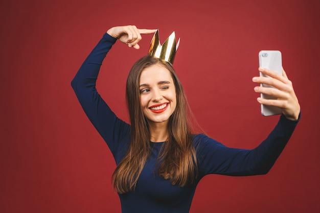 Время селфи! портрет с copyspace пустое место уверенно гордой высокомерной молодой женщины с золотой короной на голове, изолированных на красном фоне.
