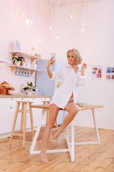 셀카 타임. 셀카를 만드는 아침에 팬티와 흰색 셔츠를 입고 짧은 컷을 가진 슬림 여성